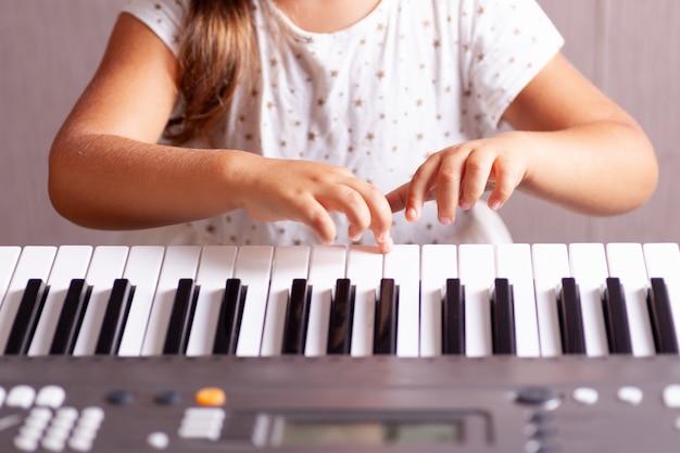 Chica con un vestido blanco tocando las teclas de un piano electrónico