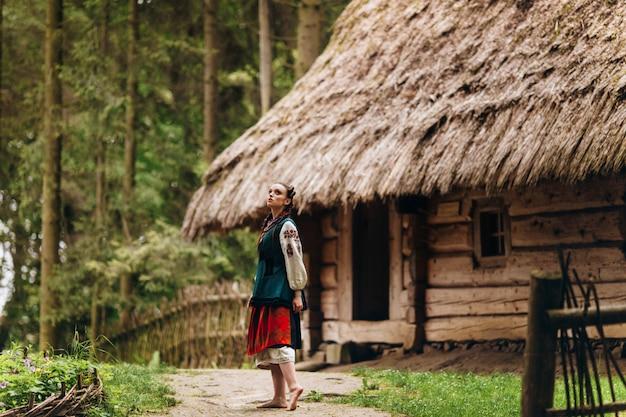 Chica con un vestido bordado está de pie en el patio y mirando hacia el cielo