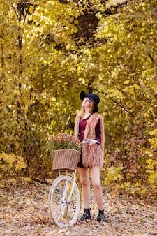 Chica en vestido burdeos y chaleco con bicicleta amarilla en un paseo a finales de otoño