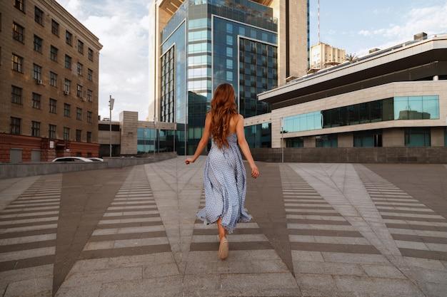 Chica en vestido corre en la ciudad. borroso