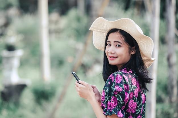Chica con un vestido de flores y con un sombrero jugando con el teléfono
