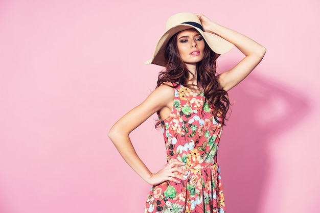 Chica en vestido de flores y sombrero de paja posando