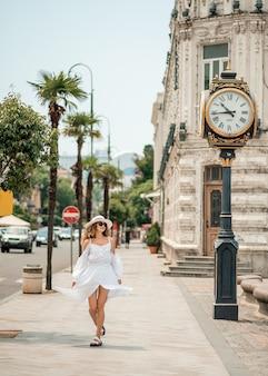 Chica con un vestido largo blanco, caminando cerca del reloj. modelo de moda muy sexy en el paisaje urbano
