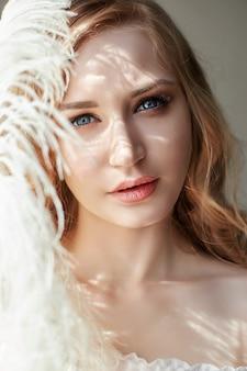 Chica en vestido de luz blanca y pelo rizado.