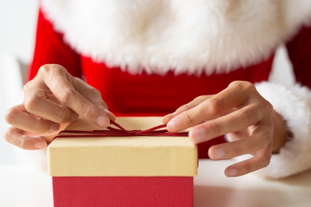 Chica en vestido de navidad envolver regalo en la mesa