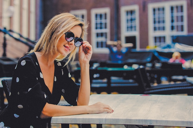 Chica en vestido negro en el cafe de amsterdam