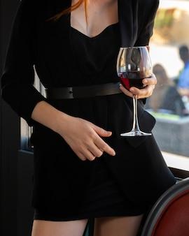 Chica en un vestido negro con una copa de vino tinto
