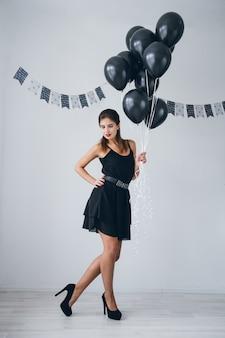 Chica en un vestido negro con globos negros