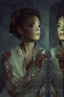 Chica en un vestido de novia cerca del espejo