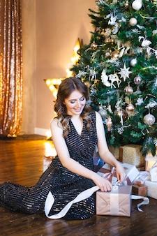 Chica en vestido oscuro de noche y árbol de navidad