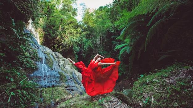 Chica con un vestido rojo bailando en una cascada.