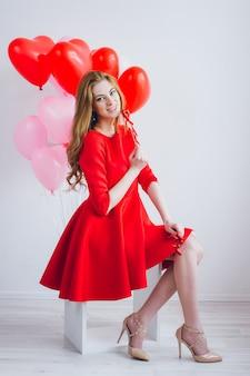 Chica en vestido rojo con globos en forma de corazón