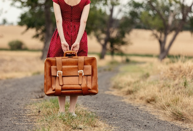 Chica de vestido rojo con una maleta en un camino rural antes de la lluvia