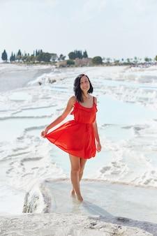Chica en vestido rojo sobre travertinos blancos