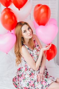 Chica en vestido romántico con globos en forma de corazón