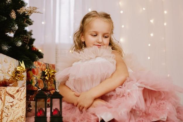 Chica con un vestido rosa cerca del árbol de navidad y cajas con regalos