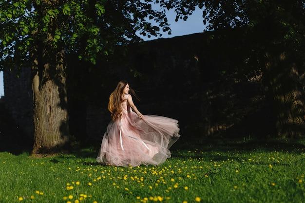 Chica en vestido rosa gira en el césped verde antes de una pared del castillo en los rayos del sol de la tarde