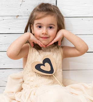 Chica en vestido sentado sobre fondo blanco de madera con un corazón en las manos