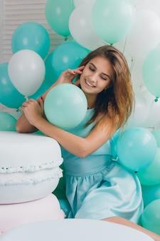 Chica en vestido turquesa con globos
