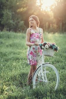 Chica en vestido de verano con bicicleta