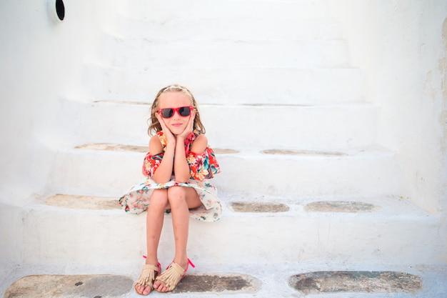 Chica en vestidos blancos divirtiéndose al aire libre en las calles de mykonos