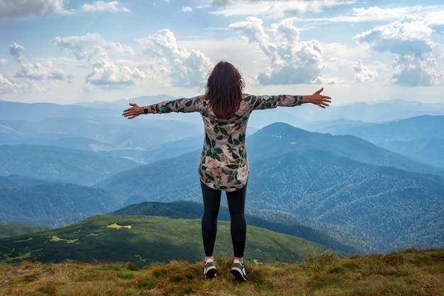 Chica viajando sola en las montañas, de pie con las manos en alto logrando la cima, le da la bienvenida a un sol.