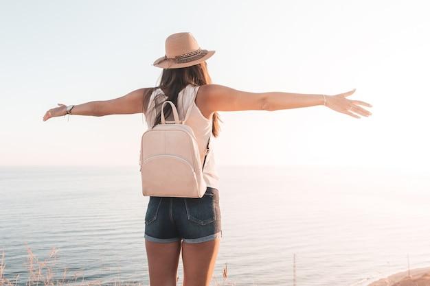 Chica de viaje o vacaciones con los brazos abiertos, mochila y sombrero mirando el horizonte