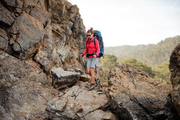 Chica viajera en gafas de sol con mochila en las montañas