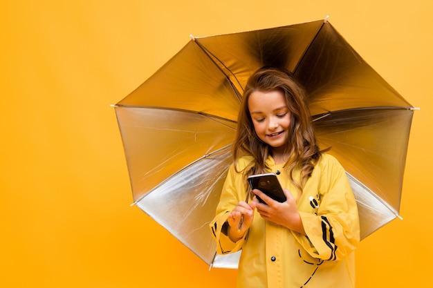 Chica viajera con un impermeable y un paraguas abierto con un teléfono en sus manos en amarillo