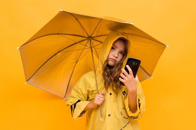 Chica viajera con un impermeable plateado y un paraguas abierto con un teléfono en sus manos sobre una pared amarilla