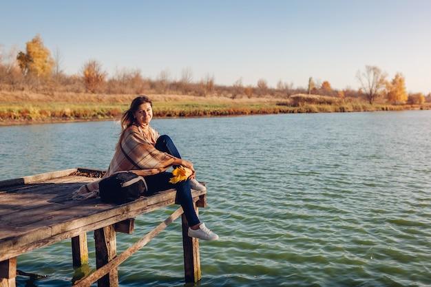 Chica viajera con mochila relajante junto al río de otoño al atardecer. mujer joven sentada en el muelle admirando el paisaje y el clima otoñal. estilo de vida activo