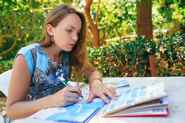 Chica viajera planificando sus vacaciones sentado a la mesa alrededor del mapa eligiendo el destino