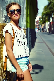 Chica viajera en ropa hipster de verano con mochila posando junto a la pared