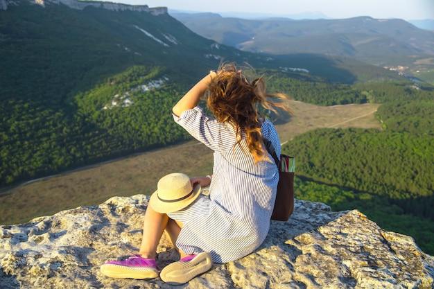 Una chica viajera se sienta en la cima de una montaña y sostiene su sombrero.