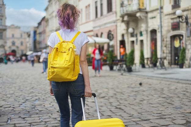 Chica viajero caminando con mochila y maleta, vista posterior.