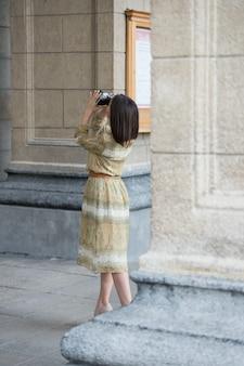 Chica de viajero haciendo cámara retro foto