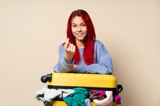 Chica de viajero con una maleta llena de ropa en la pared de color beige haciendo gesto que viene