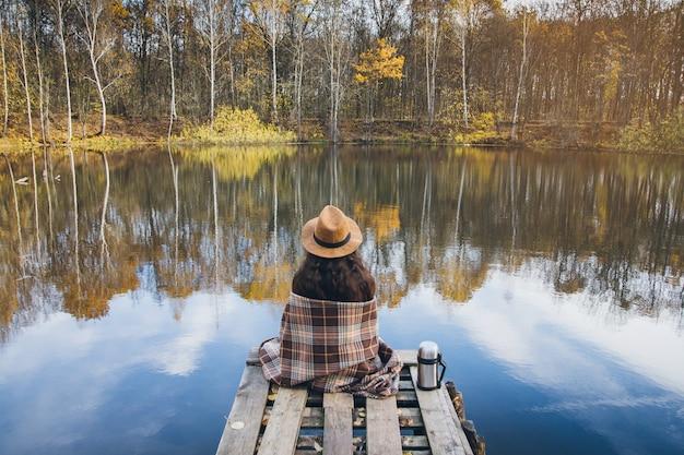 Chica en un viejo puente de madera sobre un lago