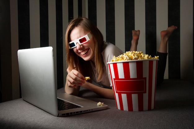 Chica viendo un programa de televisión en la noche en una computadora portátil y comiendo palomitas de maíz