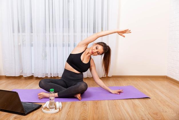 Chica viendo tutoriales de ejercicio femenino en línea usando la computadora portátil en casa