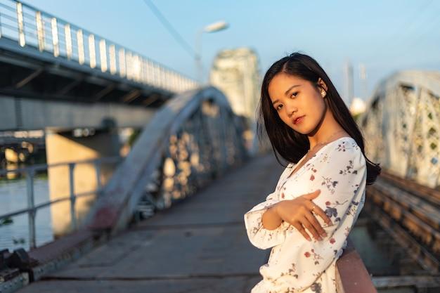Chica vietnamita de pelo negro en un puente