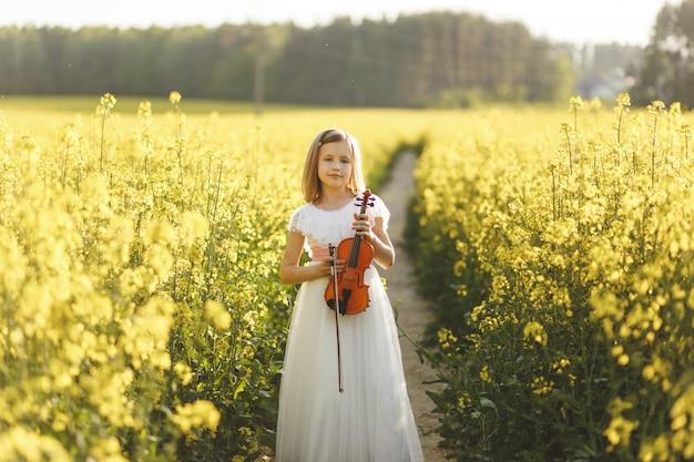 Chica con un violín en un campo en verano