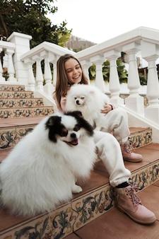 Chica de vista baja y sus perros en las escaleras