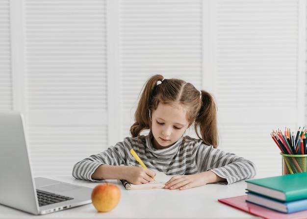 Chica de vista frontal aprendiendo de clases en línea
