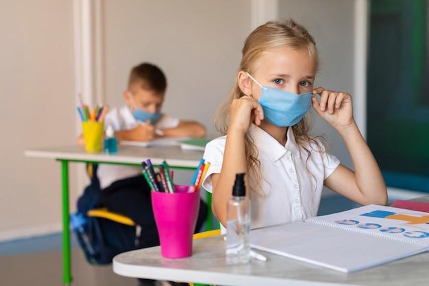 Chica de vista frontal poniéndose su máscara médica en clase