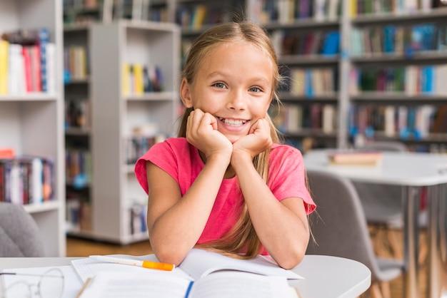 Chica de vista frontal sonriendo en la biblioteca
