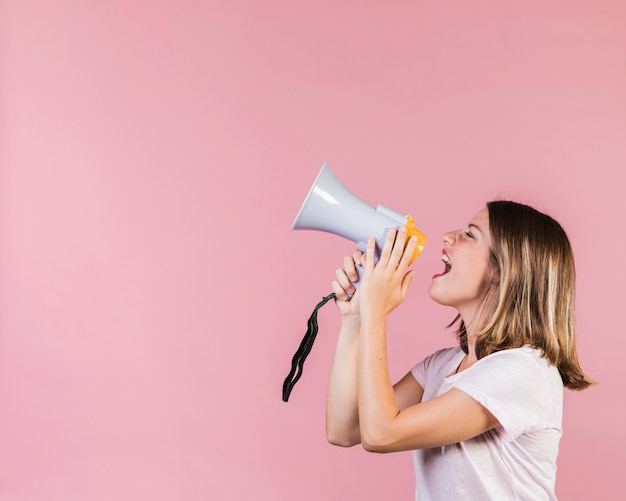 Chica de vista lateral gritando en un megáfono