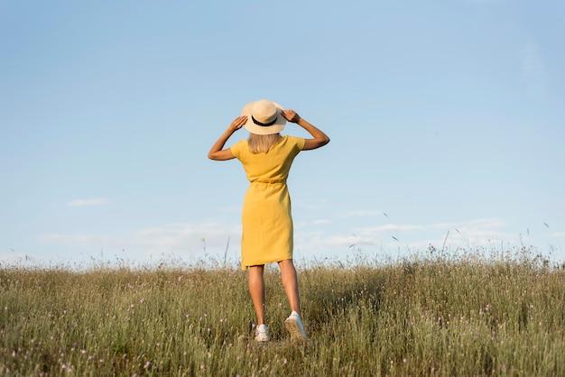 Chica de vista posterior con sombrero dando un paseo en la naturaleza