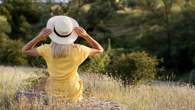 Chica de vista posterior con sombrero disfrutando de la naturaleza después de la cuarentena