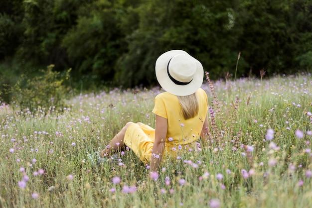 Chica de vista posterior con sombrero relajante al aire libre